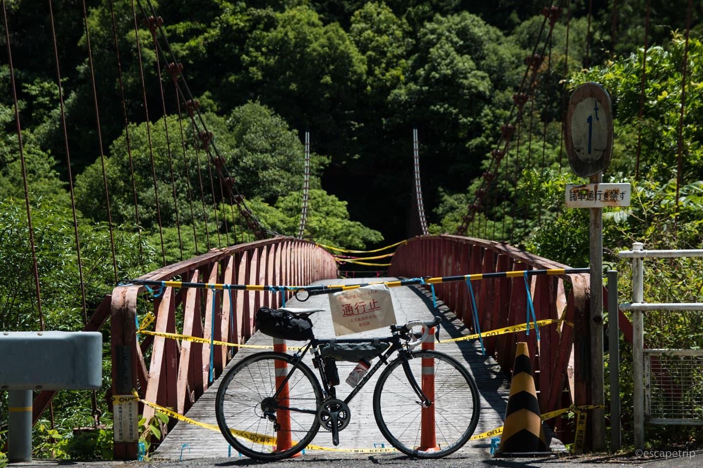 老朽化した吊橋とロードバイク