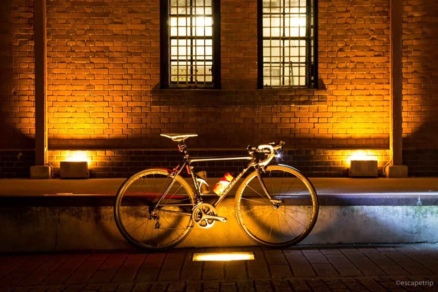 ライトアップされた赤レンガ倉庫とロードバイク