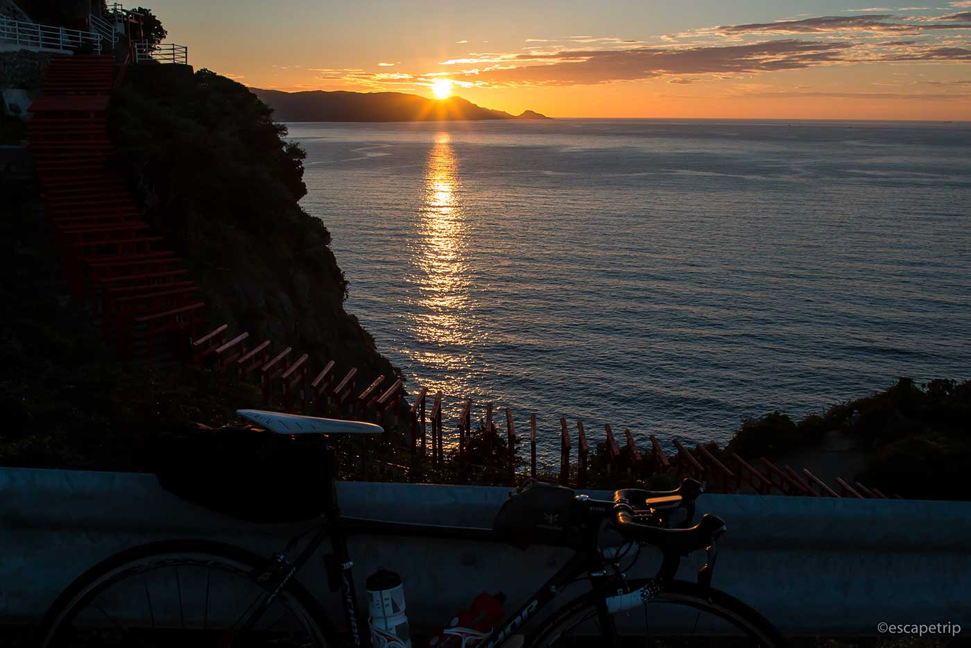 夕陽と元乃隅稲成神社とロードバイク